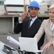 Architect and assistant stood by car with plan — Stock Photo #7750450