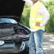 Mwearing high visibility jacket stood inspecting car engine — Stock Photo #7750498