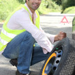 Man changing a wheel - Stock Photo