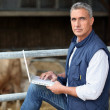 Farmer working on his laptop - Stock Photo
