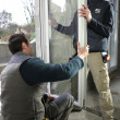 Two workers fitting window — Foto de Stock
