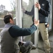 图库照片: Two workers fitting window