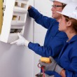 Electrical team installing a fusebox - Stock Photo