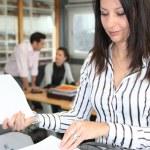 Woman using an office photocopier — Stock Photo