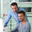 Two men working at a desktop computer — Stock Photo