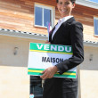 Royalty-Free Stock Photo: Estate agent with a vendu sign