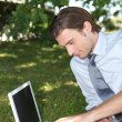 Smart male executive using a laptop with a blank screen in the park — Stock Photo
