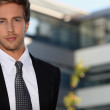 Young businessman outside a modern office building — Stock Photo