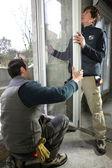 Dos trabajadores montaje ventana — Foto de Stock