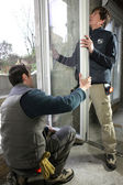 Two workers fitting window — 图库照片