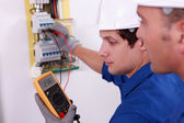 Two technical engineers checking electrical equipment — Stockfoto