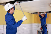 Two electricians repairing ceiling wiring — Stock Photo