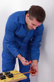 Man tightening vice on to copper pipe — Stock Photo