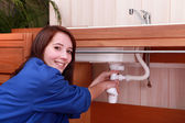 Young woman plumbing a sink — Stock Photo