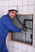 Young plumber working in bathroom — Stock Photo