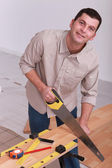 Man sawing wooden floorboards — Stock Photo