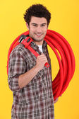Plumber holding wrench and length of plastic pipe — Stock Photo