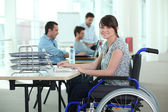 Woman in wheelchair with laptop computer — Stock Photo