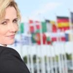 Businesswoman next to flags — Stock Photo #7780385