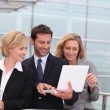 Business team looking at a laptop outside a glass building — Stock Photo #7780409