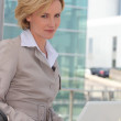 Businesswoman on laptop outside airport — Stock Photo #7780481