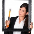 Woman with a hammer and a picture frame - Stock Photo