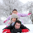 Family laying down in the snow — Stock Photo