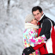 Couple in ski jackets hugging on a winter's day - Foto de Stock