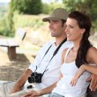 Couple with camera sat on bench - Stock Photo