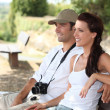 Couple with camera sat on bench — Stock Photo