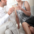 Couple sitting holding champagne glasses — Stock Photo
