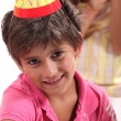 Stock Photo: Young boy in birthday party hat