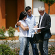 Estate-agent about to show couple around property - Stock Photo