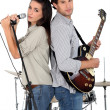 Stock Photo: Woman singing whilst man plays guitar