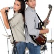 Woman singing whilst man plays guitar — Stock Photo