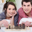 Young man and young woman playing chess - Stock Photo