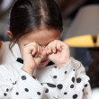Little girl rubbing her eyes - Stockfoto