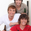Stock Photo: Three lads with bottles of beer