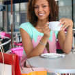 20 years old metis woman is drinking coffee on a terrace, she did shopping — Stock Photo
