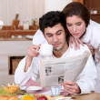 Young couple reading a newspaper at breakfast — Stock Photo #7786544