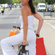 Woman with store bags riding a bike in the city - Stock Photo