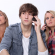Stock Photo: Three teenager using mobile telephones