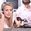 Teenagers listening to music on headphones - Stock Photo