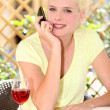 Stock Photo: Womdrinking glass of wine on terrace
