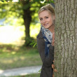 Woman hiding behind a tree — Stock Photo #7788516