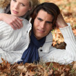 Couple laying in fallen leaves — Stock Photo