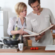 Couple cooking together with a recipe book — Stock Photo #7788996