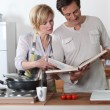 Stock Photo: Couple cooking together with recipe book