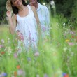 Stock Photo: Happy young couple in high grass amid wild flowers