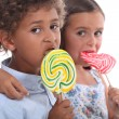 Couple of children with lollypops - Stock Photo